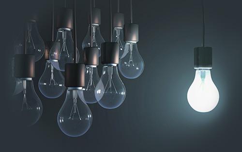 Groupe d'ampoules éteintes face à une ampoule allumée